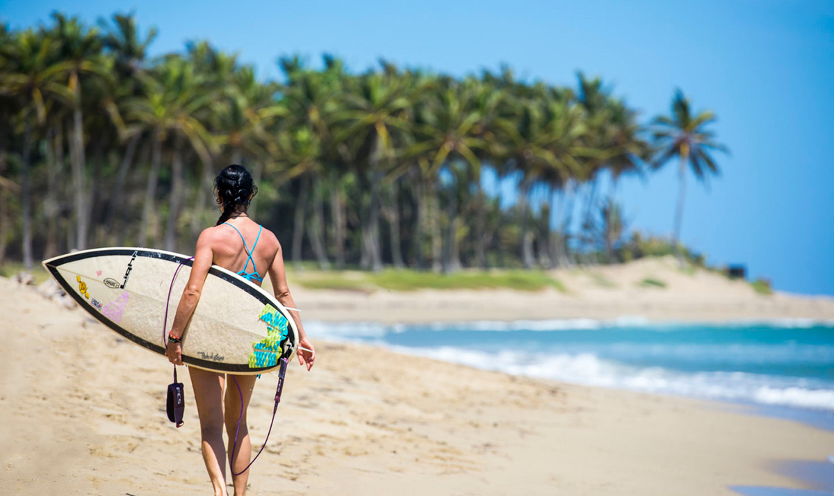 Woman on Beach with Surfboard in Dominican Republic